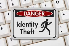 Id Theft sign laying on top of keyboard